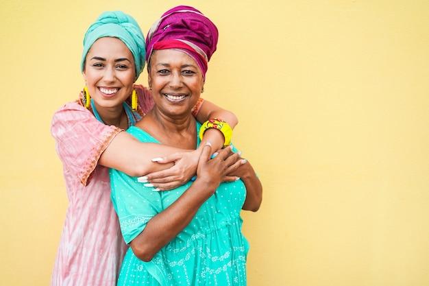 Feliz mãe e filha com vestidos tradicionais africanos sorrindo para a câmera. foco nos rostos