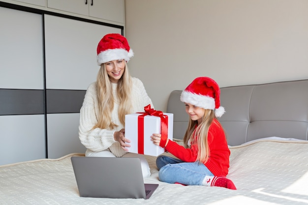 Feliz mãe e filha comemorando amigos com videochamada. celebração de natal online