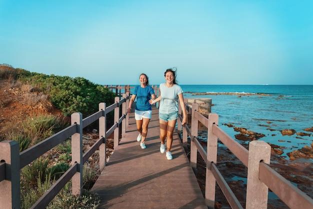 Feliz mãe e filha correndo na calçada à beira-mar. mulher de meia-idade sorridente e adolescente de mãos dadas e caminhando ao pôr do sol, tiro de corpo inteiro. maquete de camiseta