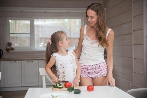Feliz mãe e filha cozinhando juntas