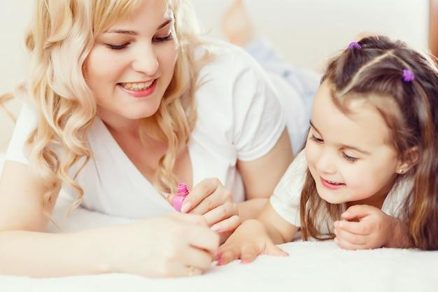 Feliz mãe e filha criança em rolos de cabelo pintar as unhas