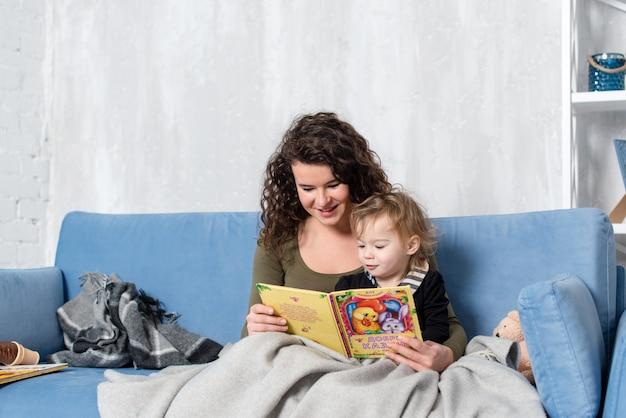 Feliz mãe e filha da família lê um livro pela manhã em casa