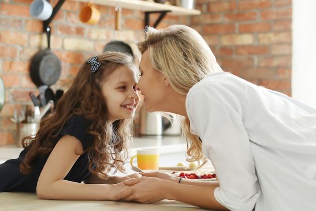 Feliz mãe e filha de mãos dadas na cozinha