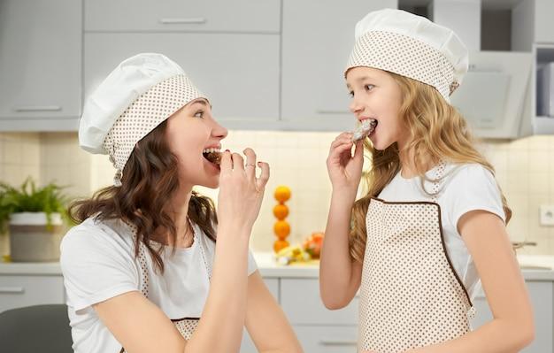 Feliz mãe e filha degustação de biscoitos caseiros.