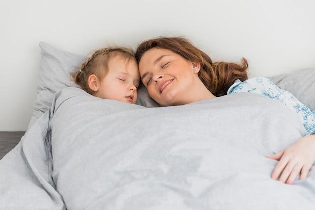 Feliz mãe e filha dormindo juntos em casa