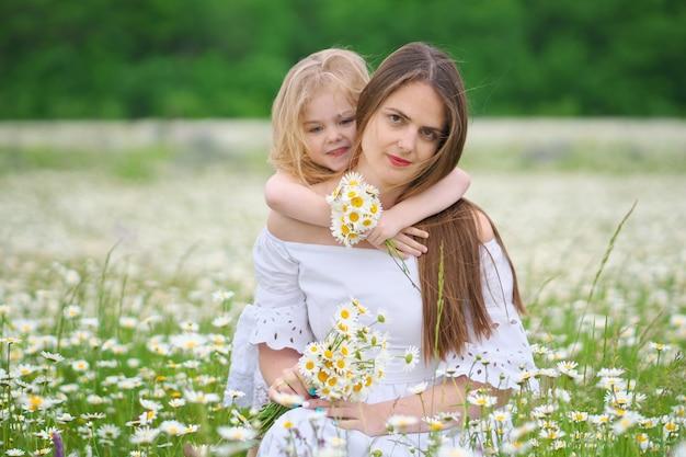 Feliz mãe e filha em prado de camomila.