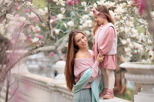 Feliz mãe e filha em uma caminhada no parque em roupas cor de rosa se divertindo sob as árvores de magnólia.