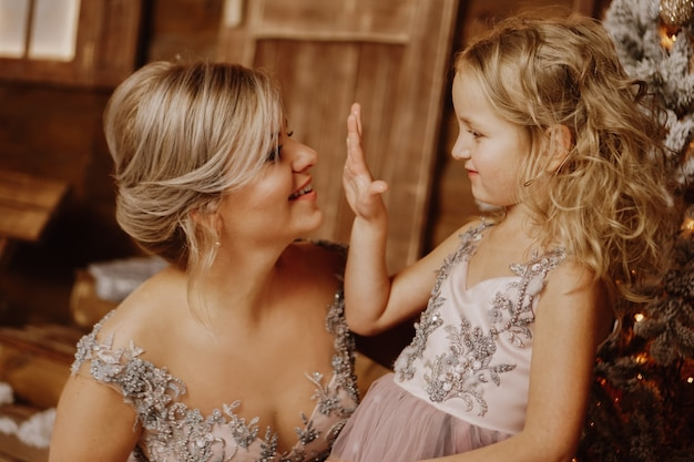 Feliz mãe e filha em vestidos rosa perto das decorações de natal