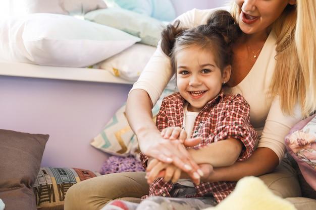 Feliz, mãe e filha estão brincando no quarto perto da janela, vestida com roupas casuais