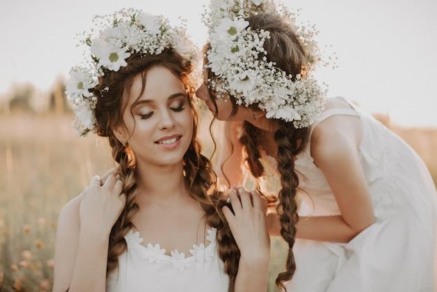 Feliz, mãe e filha estão sorrindo e abraçando no campo no verão em vestidos brancos com tranças e grinaldas florais