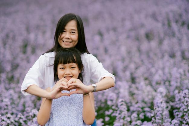 Feliz mãe e filha fazendo sinal de coração e sorrindo em um lindo campo de flores.