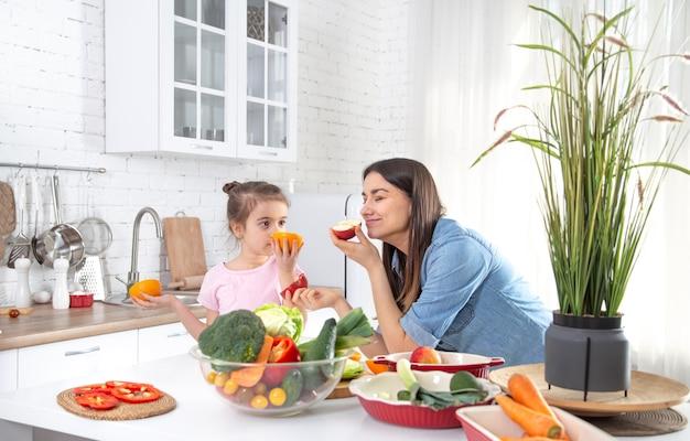Feliz mãe e filha gostam de cozinhar em uma cozinha espaçosa e bem iluminada.