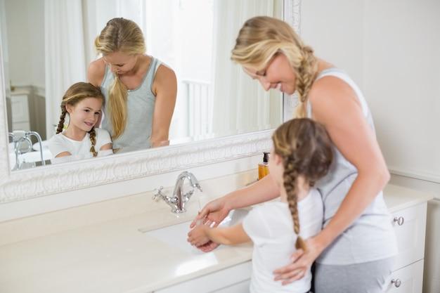 Feliz mãe e filha lavando as mãos na pia do banheiro