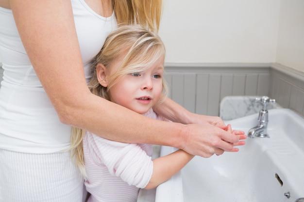 Feliz mãe e filha lavando as mãos