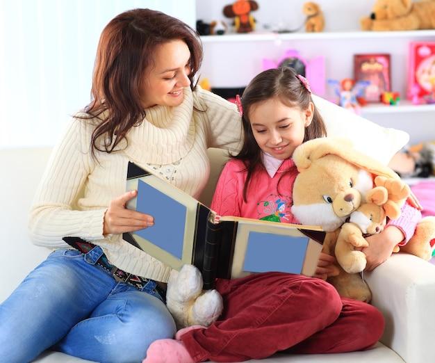 Feliz mãe e filha lendo um livro juntas