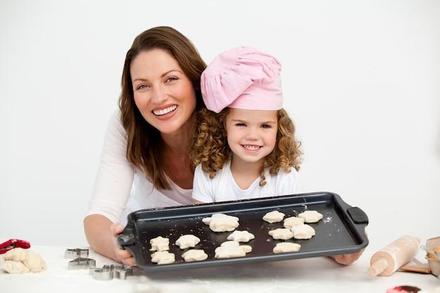 Feliz mãe e filha mostrando um prato com biscoitos