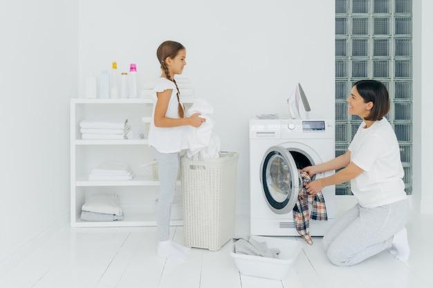 Feliz mãe e filha ocupada lavando roupa em casa