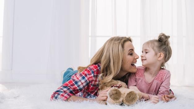Feliz mãe e filha olhando uns aos outros