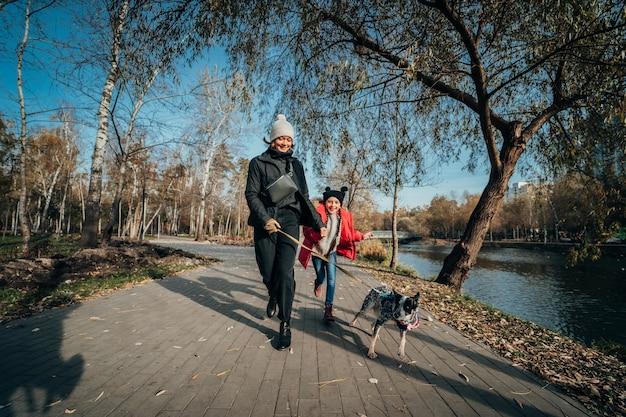 Feliz mãe e filha passear com cachorro no parque outono