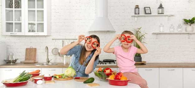 Feliz mãe e filha posando com anéis de pimenta enquanto cozinham a salada.