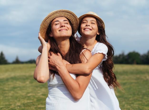 Feliz mãe e filha posando na natureza