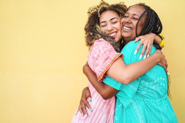 Feliz mãe e filha se abraçando com a parede amarela - família, maternidade e conceito de amor