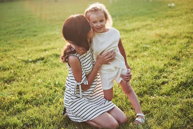 Feliz mãe e filha se abraçando em um parque ao sol em um fundo de verão brilhante de ervas.