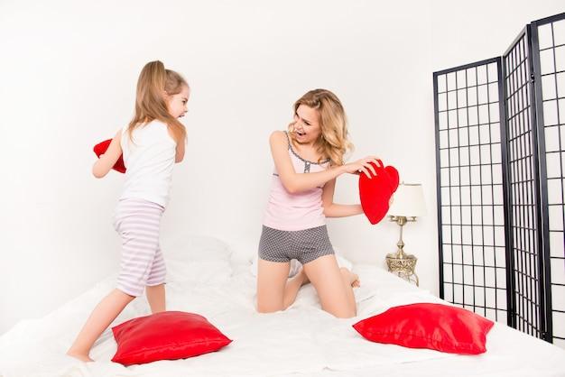 Feliz mãe e filha se divertindo e lutando com os travesseiros