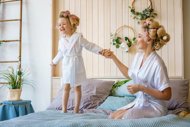 Feliz mãe e filha se divertindo na cama em roupões