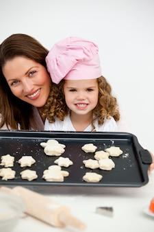 Feliz mãe e filha segurando um prato com biscoitos