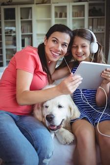 Feliz mãe e filha sentada com cachorro e ouvindo música em fones de ouvido