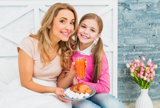 Feliz mãe e filha sentada com croissant na cama
