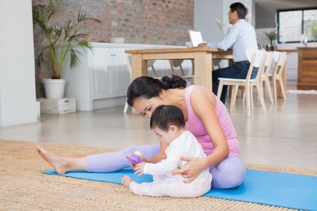 Feliz mãe e filha sentada no tapete de exercício em casa
