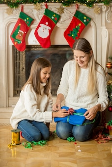 Feliz mãe e filha sentadas no chão junto à lareira e embalando uma camisola para o presente de natal