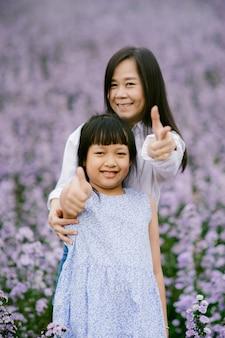 Feliz mãe e filha sorrindo em um lindo campo de flores.