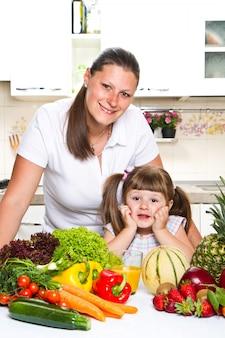 Feliz mãe e filha sorrindo na cozinha