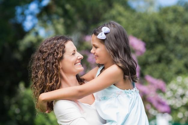 Feliz mãe e filha, sorrindo para o outro