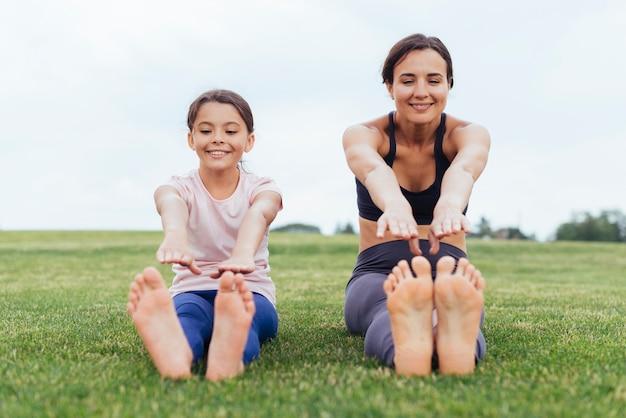 Feliz mãe e filha tocando os dedos dos pés na natureza