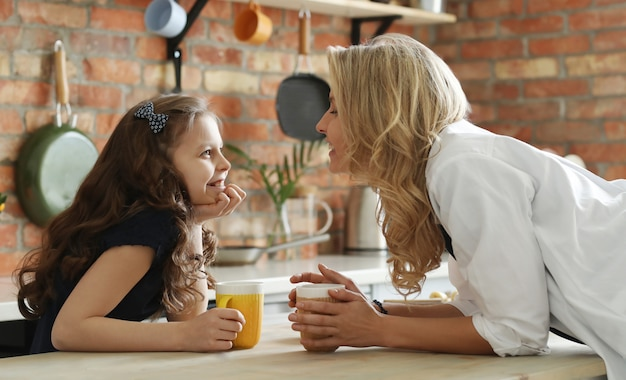 Feliz mãe e filha tomando café na cozinha
