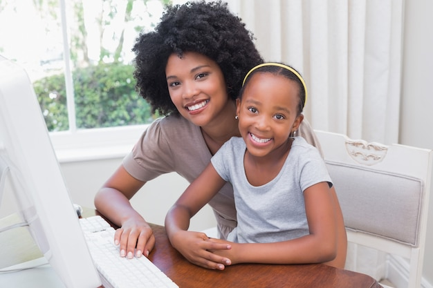 Feliz mãe e filha usando o computador