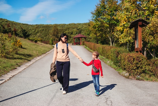 Feliz mãe e filho caminhando na natureza