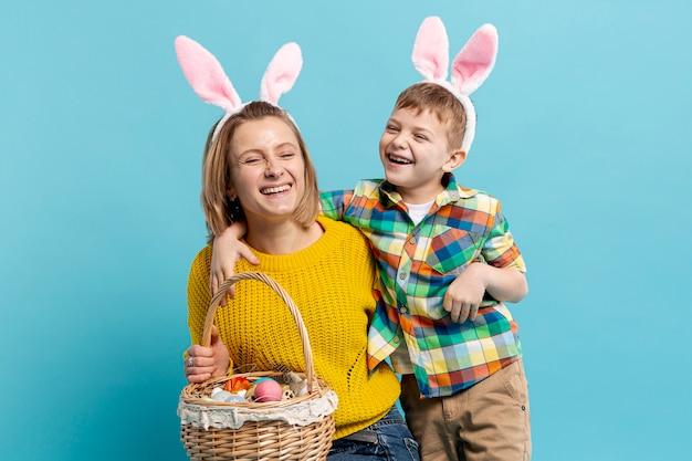 Feliz mãe e filho com cesta de ovos pintados