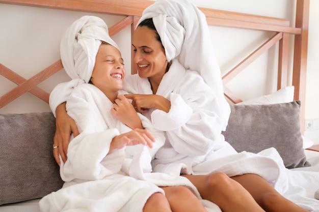 Feliz mãe e filho descansando após o banho no quarto