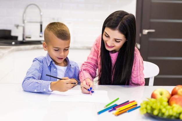 Feliz mãe e filho desenhando com lápis de cor está se divertindo em casa