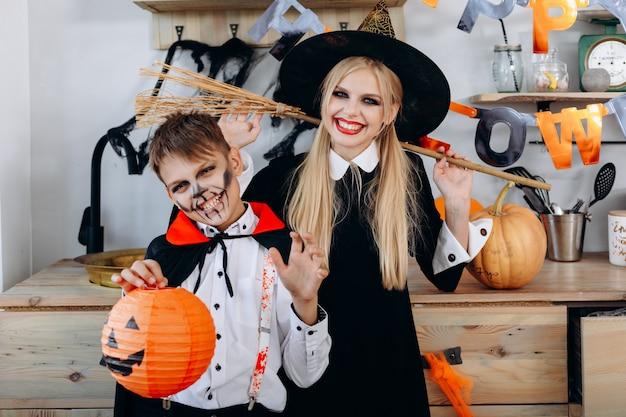 Feliz mãe e filho em pé no vestido extravagante, segurando pumpking e vassoura