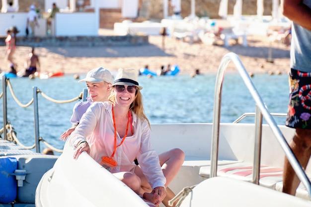 Feliz mãe e filho em um barco no fundo da praia.