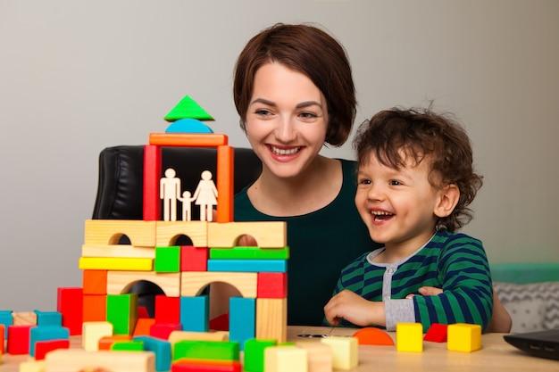 Feliz, mãe e filho estão brincando e construindo uma casa para a família. eles colocaram um telhado.