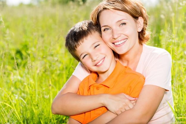 Feliz mãe e filho no retrato ao ar livre do prado primavera