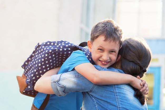 Feliz mãe e filho se abraçam na frente da escola primária.