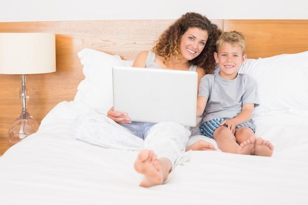 Feliz mãe e filho sentado na cama com laptop